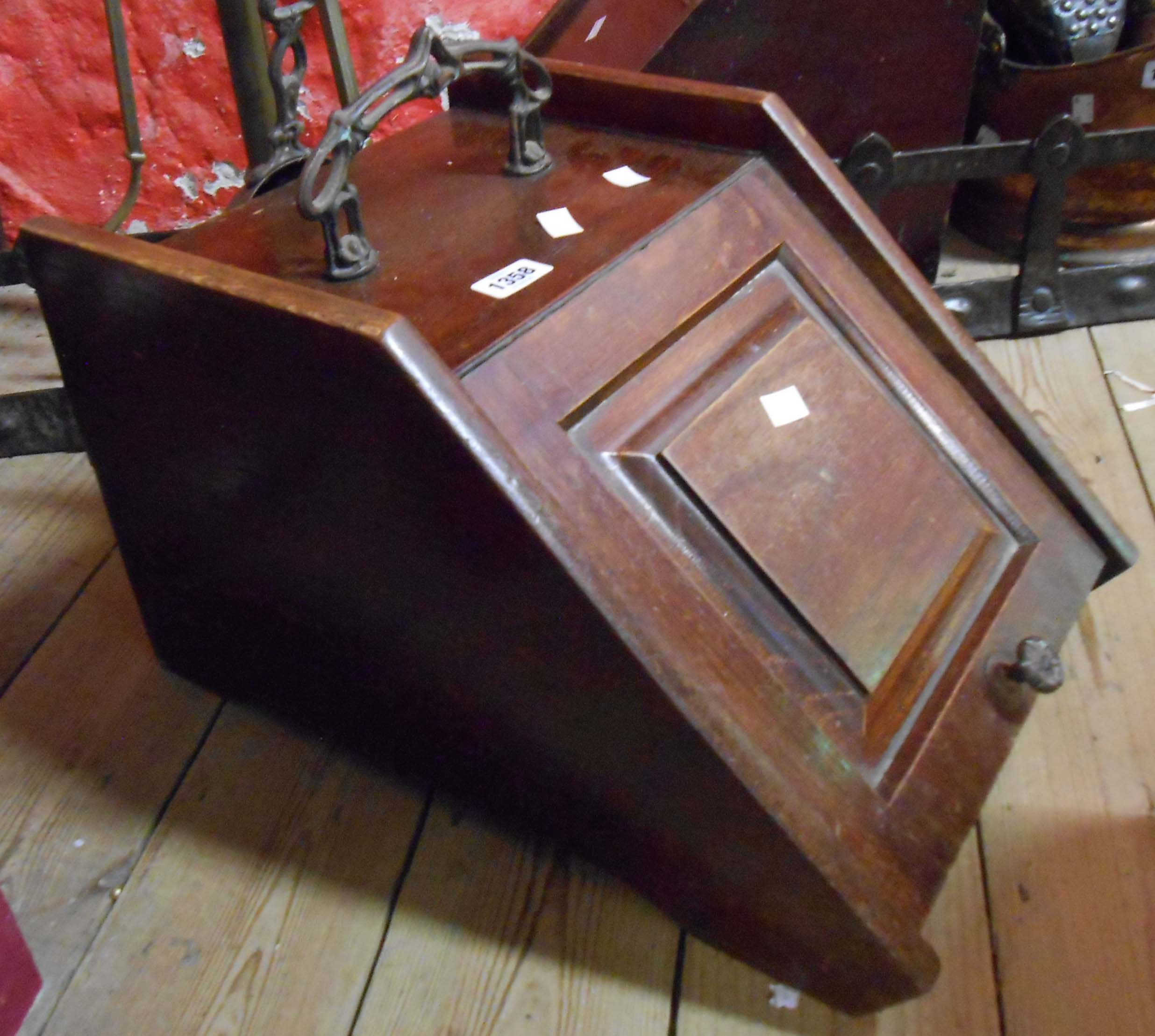 A wooden coal box with decorative cast iron handle and shovel