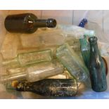 A box containing a selection of old glass bottles including Plymouth and Exeter examples