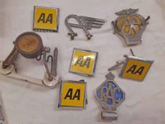 A box containing assorted car related collectables including AA and RAC badges, Alvis bonnet mascot,