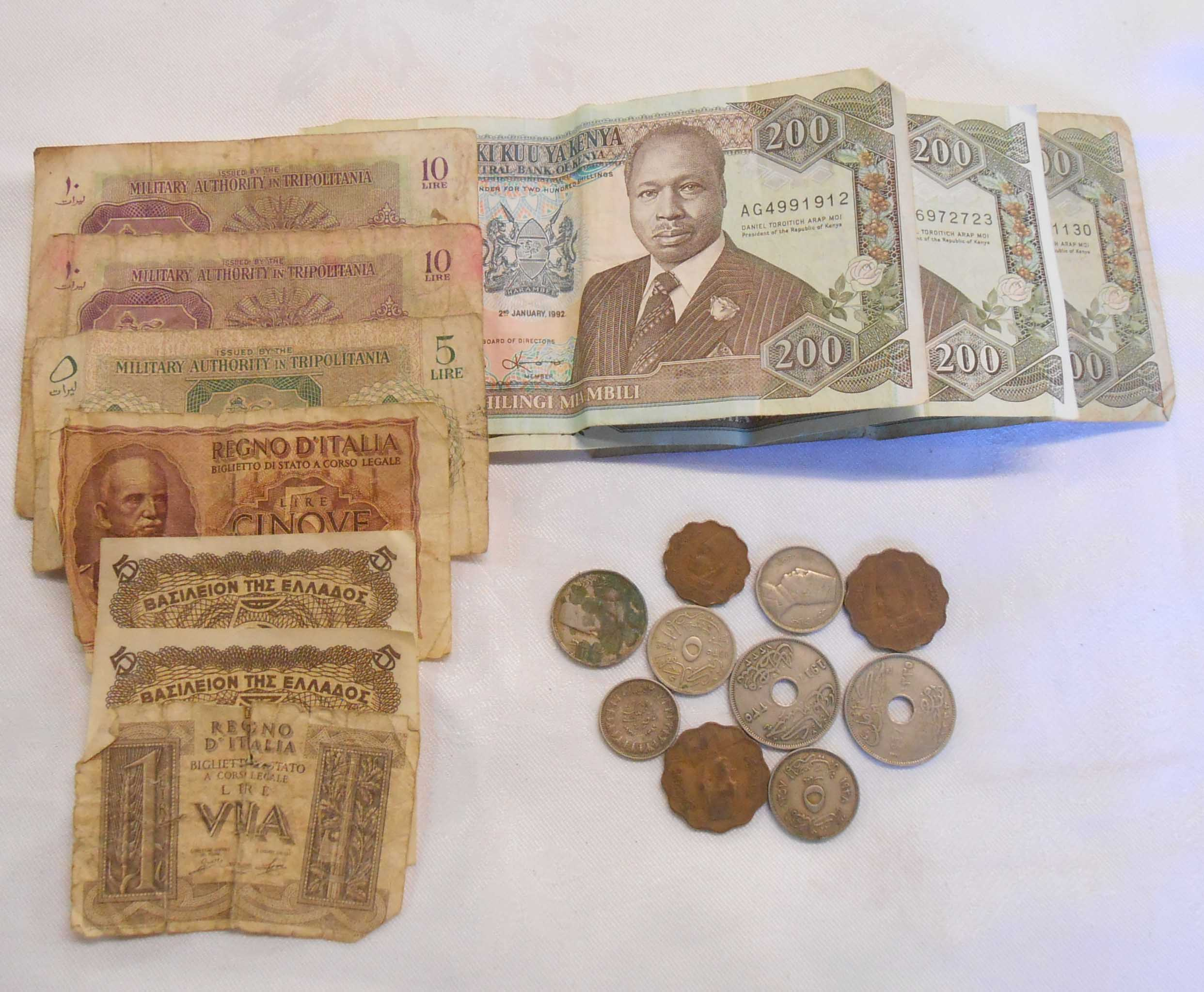 A tin containing assorted foreign banknotes and coins including Kenya, Italy, Libya (military
