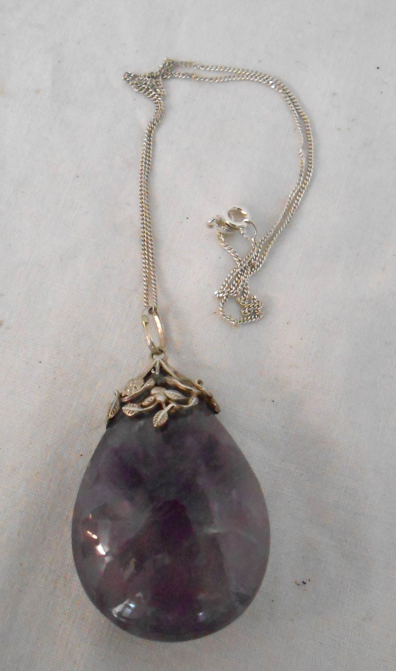 A white metal mounted polished amethyst large drop pendant, on marked 925 chain