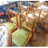 A set of four reproduction yew wood framed sabre leg dining chairs with upholstered drop-in seats