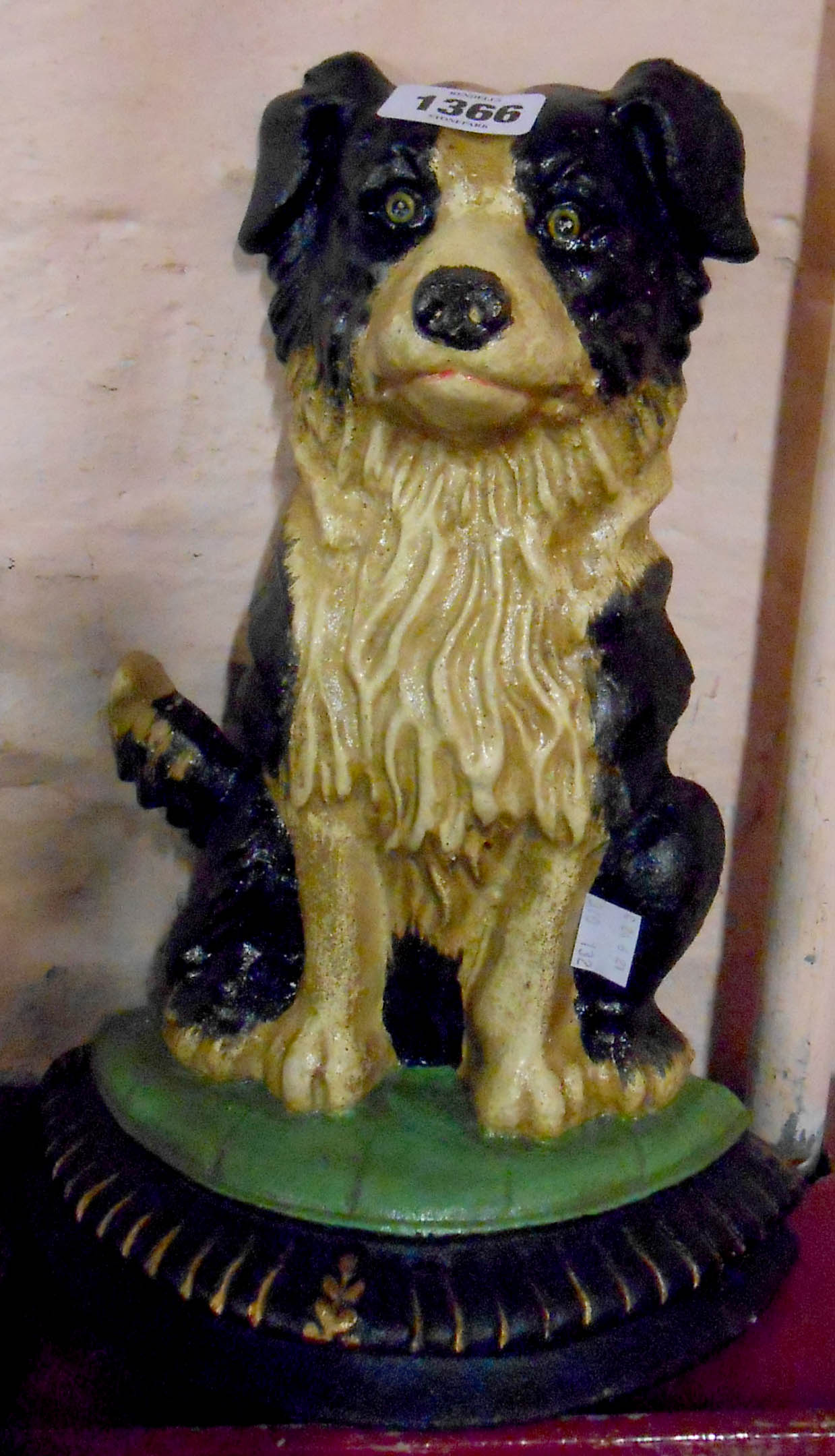 A cast metal and painted doorstop in the form of a seated collie dog