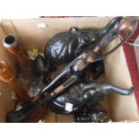 A box containing assorted carved wood items including a troop of seven graduated ebony elephants,
