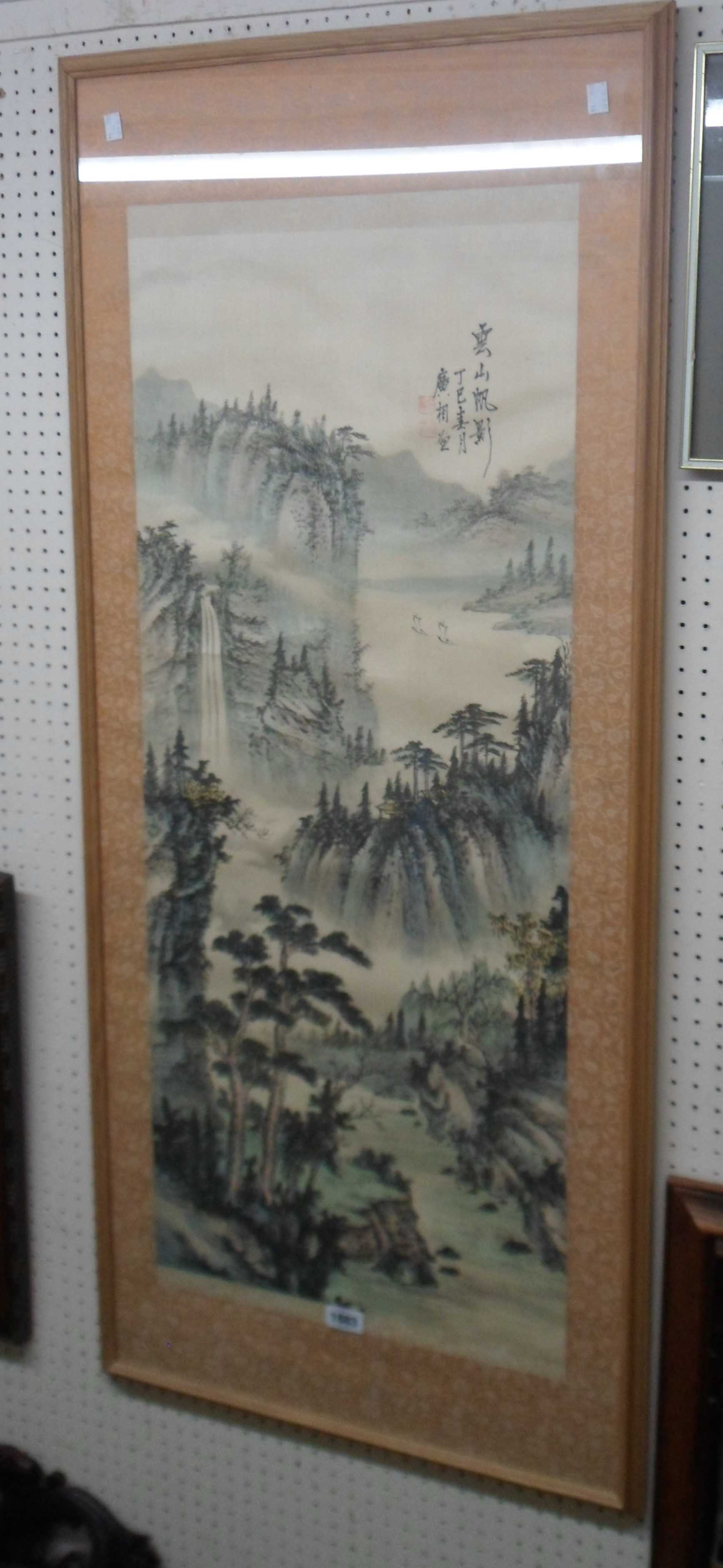 A framed 20th Century Chinese painted silk mountain river landscape picture within a material border