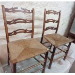 A pair of old stained beech framed pierced ladder back standard chairs with remains of woven rush