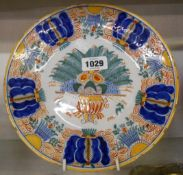 An 18th Century Dutch Delft plate hand painted in polychrome with a large central floral urn