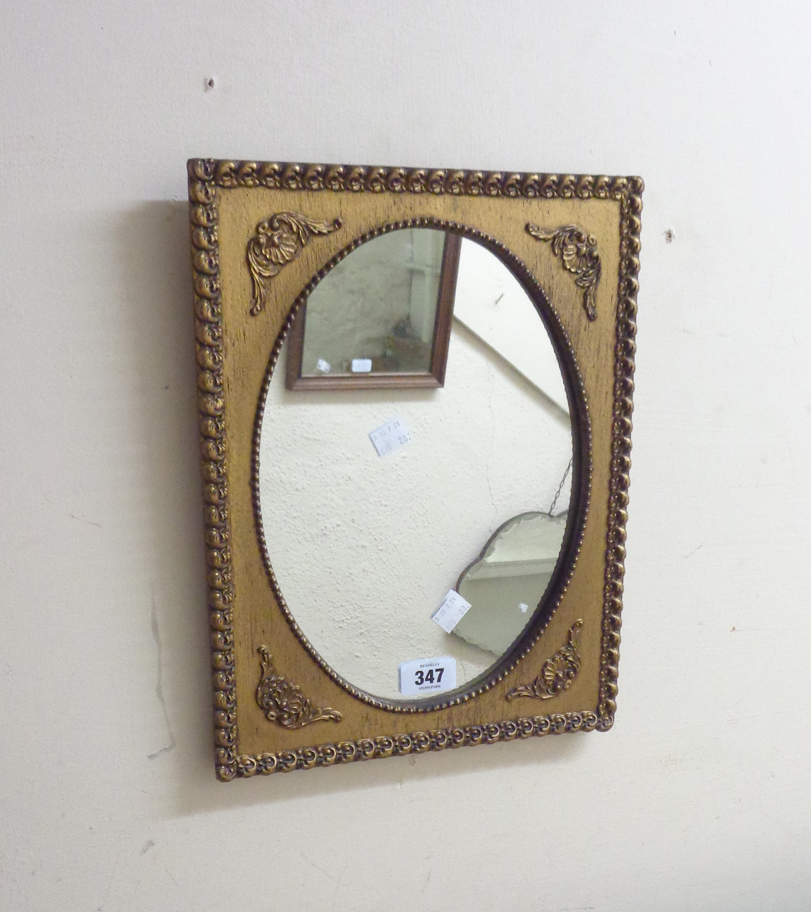 A vintage small gilt framed wall mirror with applied decoration and oval plate