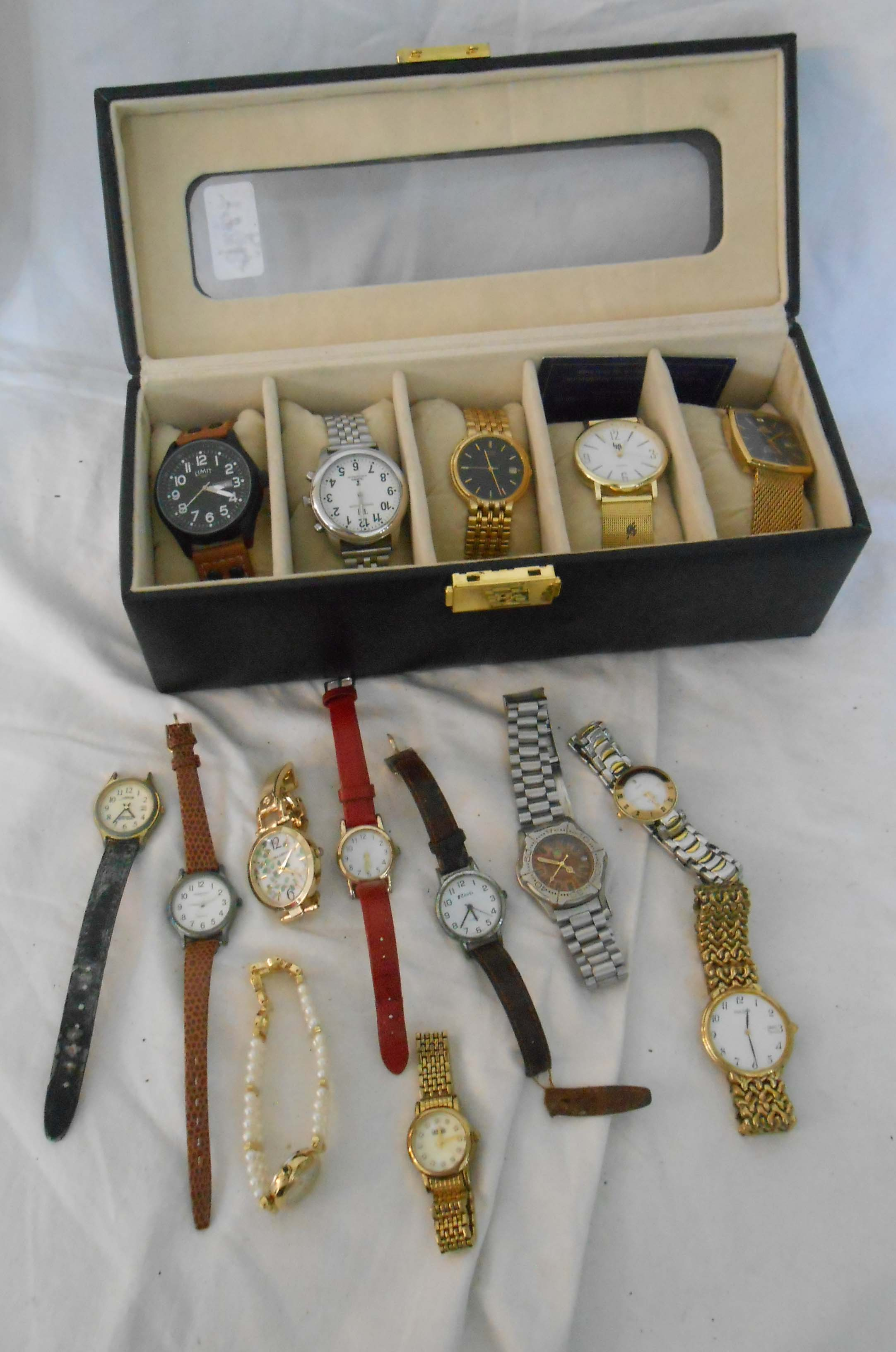A upholstered case containing a collection of assorted wristwatches