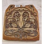 An antique wooden printing stamp block with filagree metal design depicting a pair of Heraldic lions