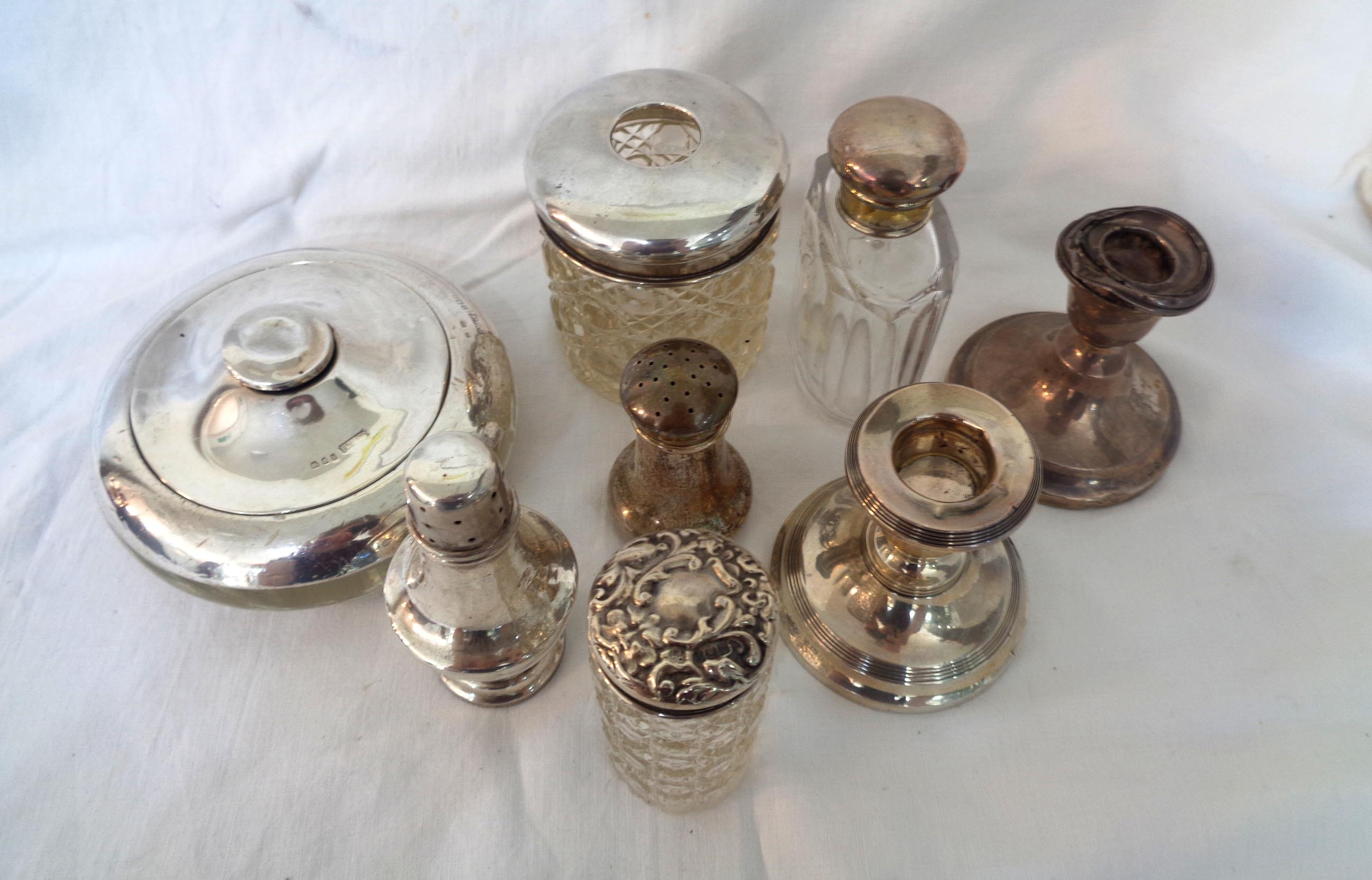 Various silver topped dressing table glass jars, two damaged candlesticks and two pepperettes -