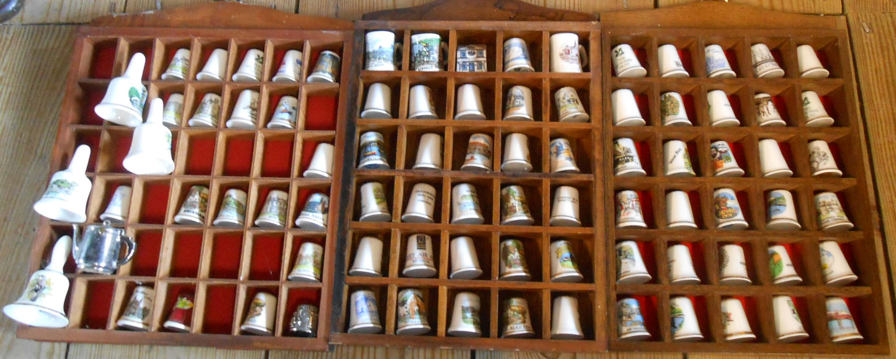 Three racks of mainly ceramic collectable thimbles