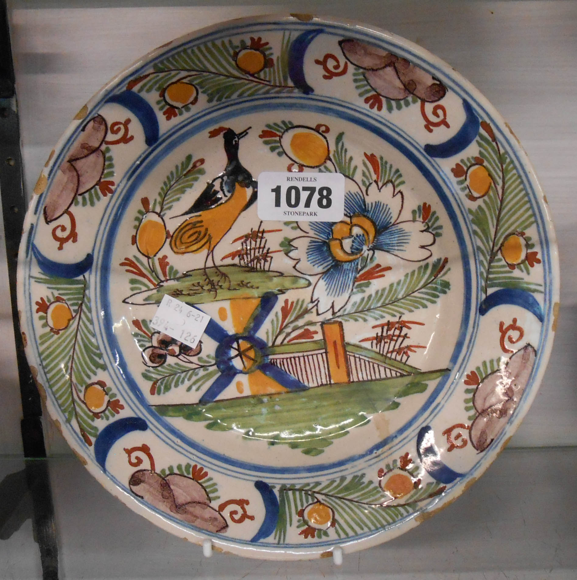 An 18th Century Bristol Delftware plate, depicting a bird sitting on a fence - old restoration