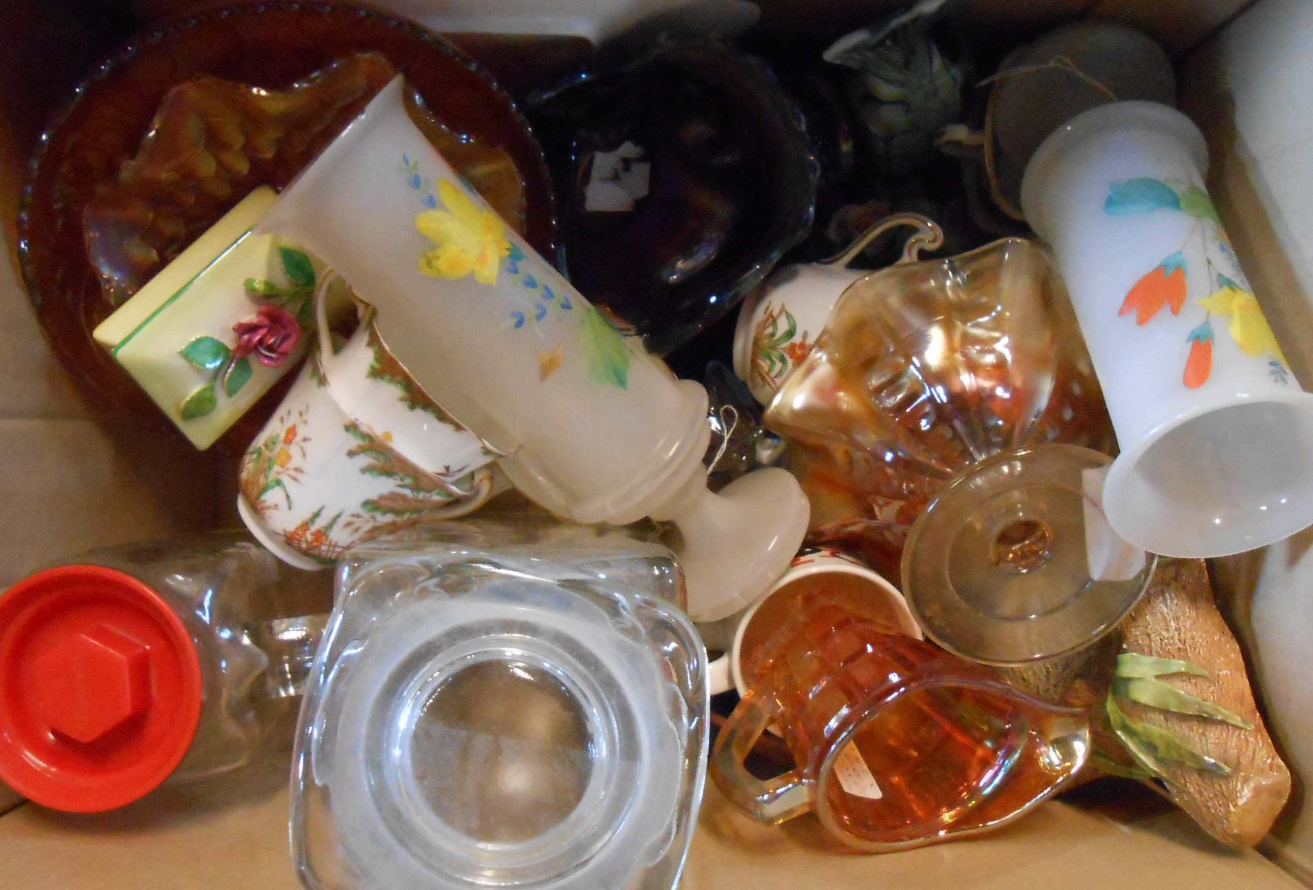 A box containing assorted ceramics and glass including carnival glass, golly mugs, teaware, etc.
