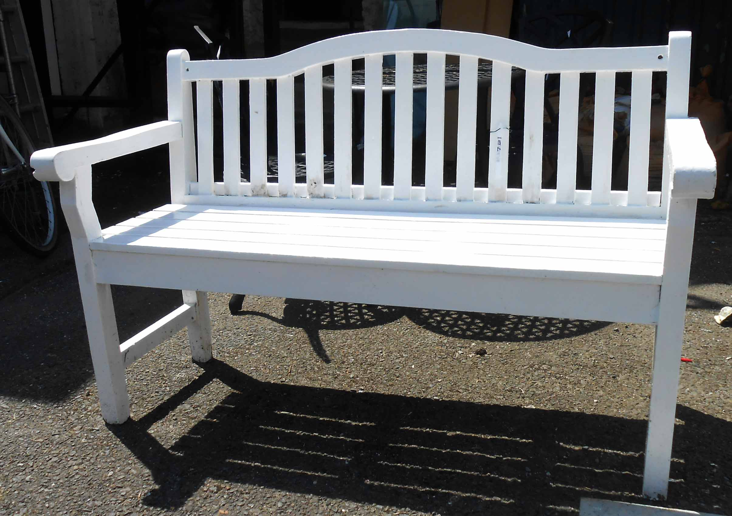 A two seater wooden white painted garden bench