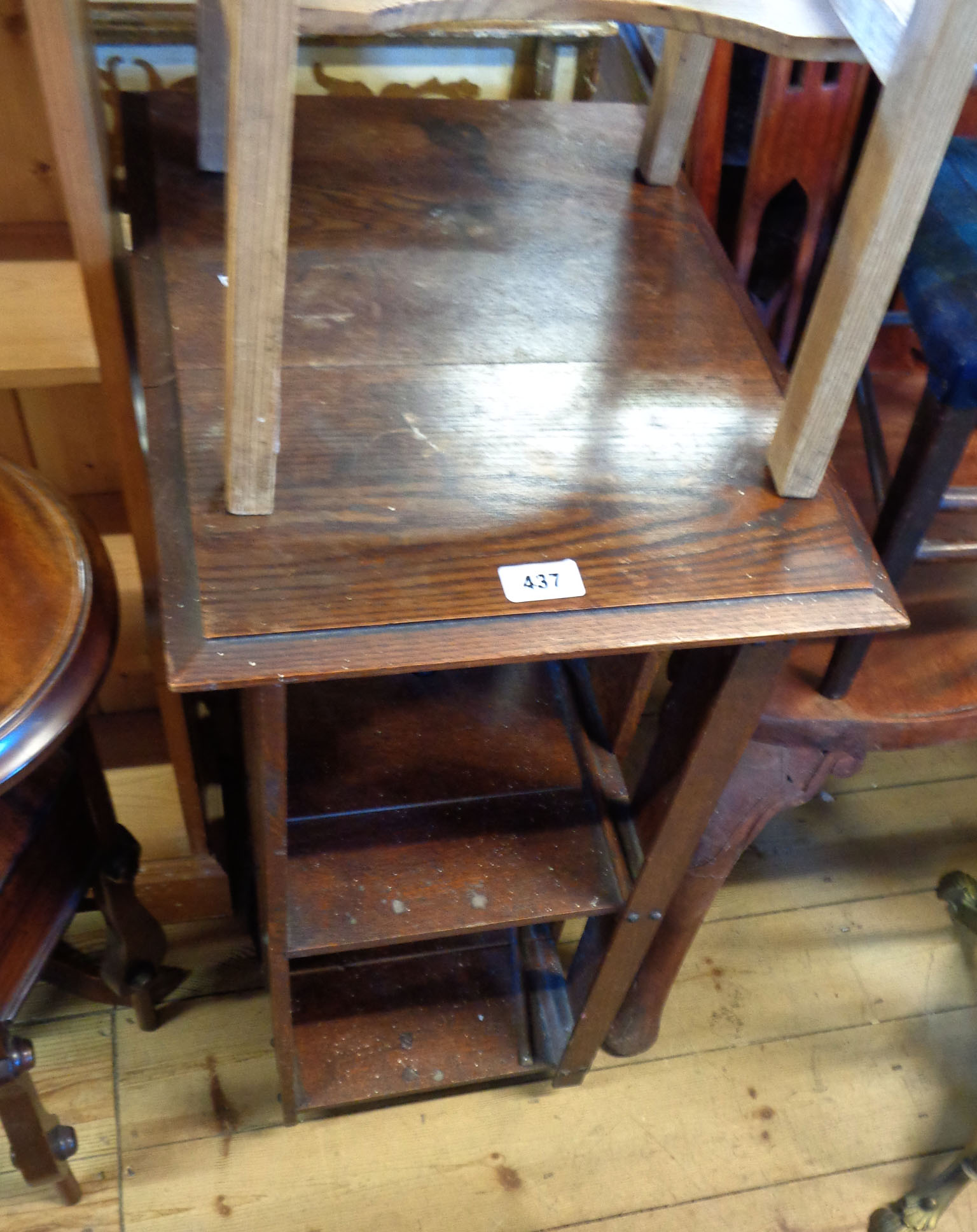 An old stained oak revolving bookcase with slatted sides and dividers