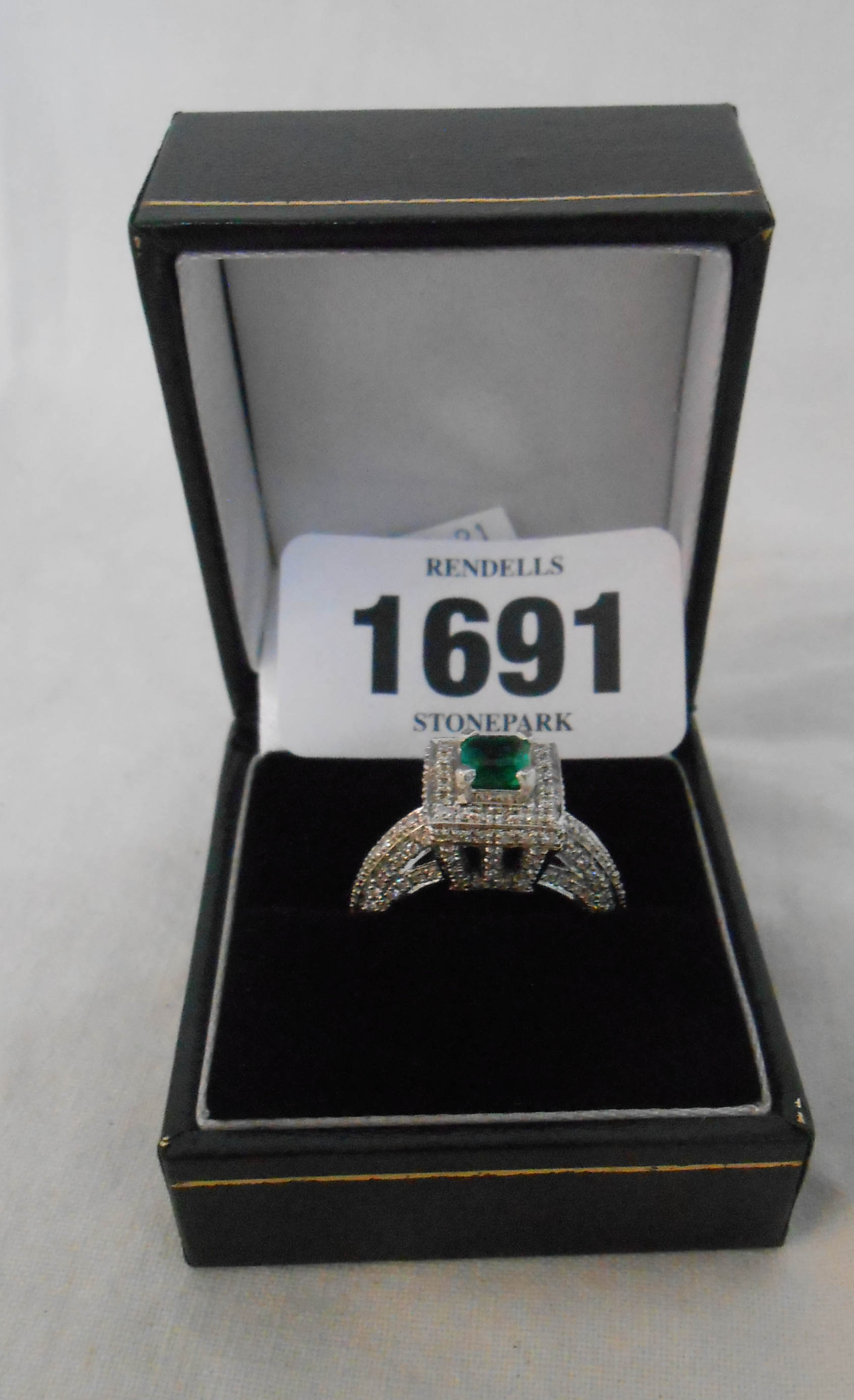 A hallmarked 585 white gold square panel ring, set with central emerald within a diamond border with