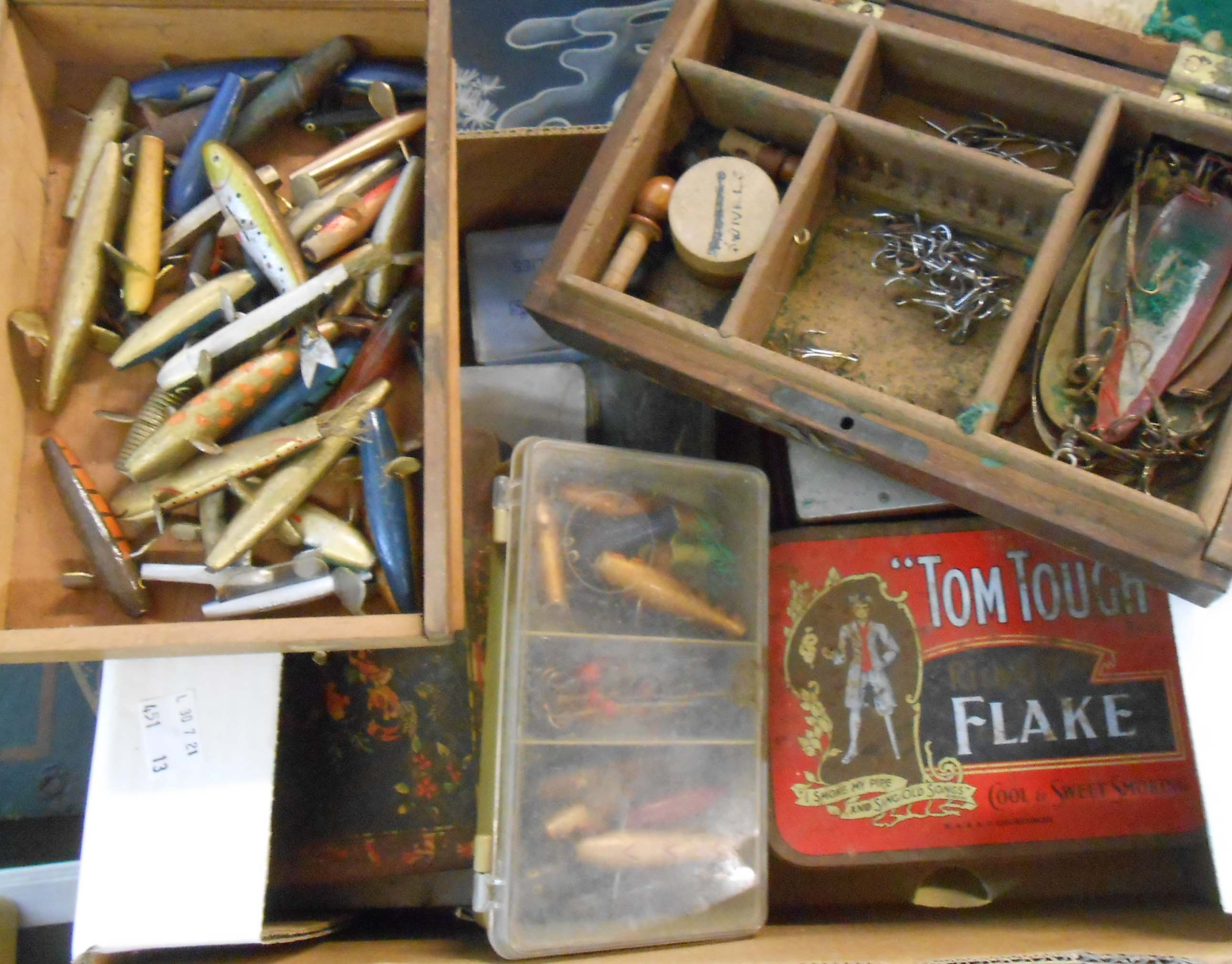 A box containing a collection of vintage fishing lures, spinners and spoons, etc.