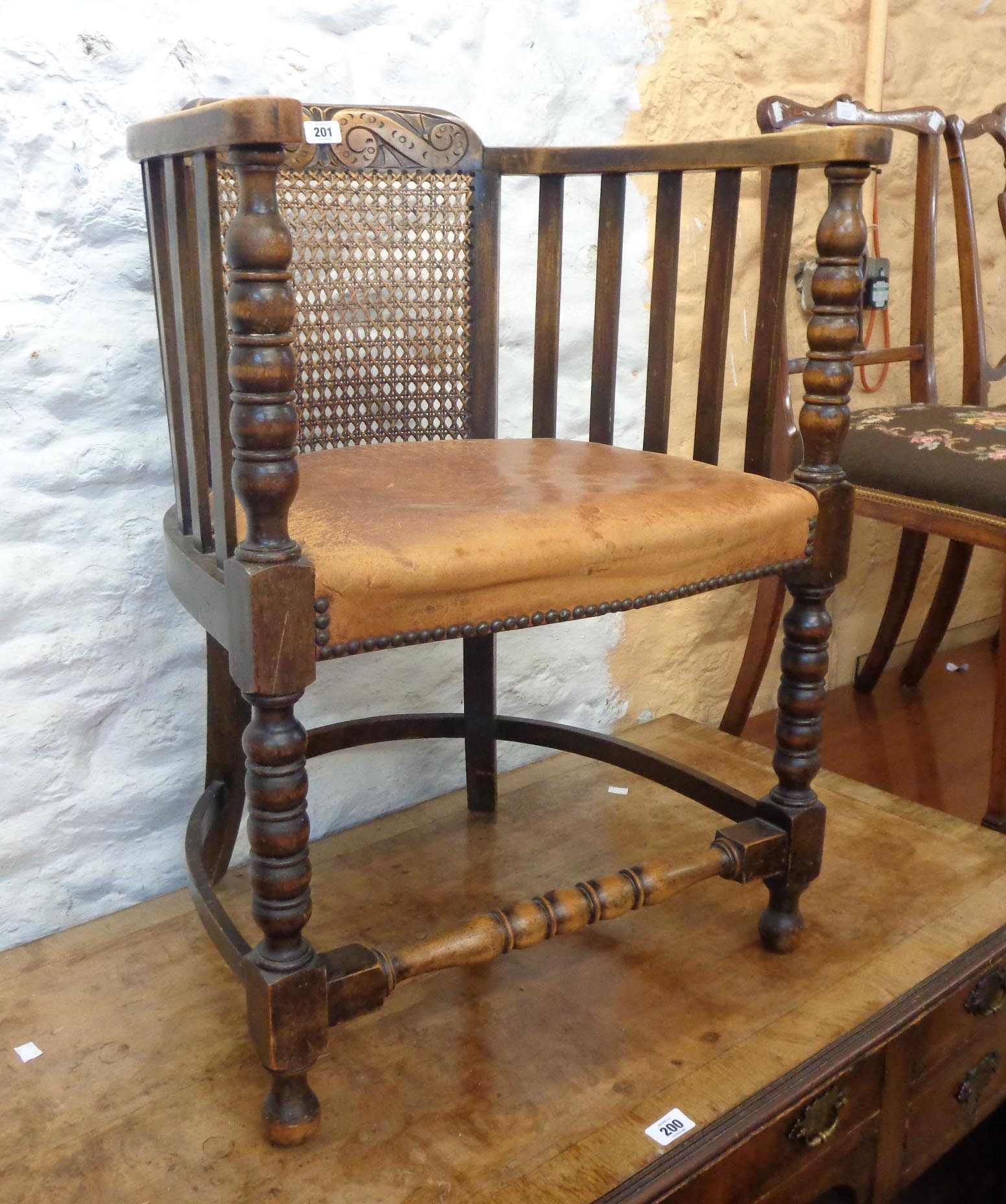 A 1920's oak framed tub elbow chair with remains of studded leather upholstery, set on bobbin turned