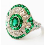 A marked PLAT Art Deco style curved panel ring, set with various cut emeralds and diamonds in a