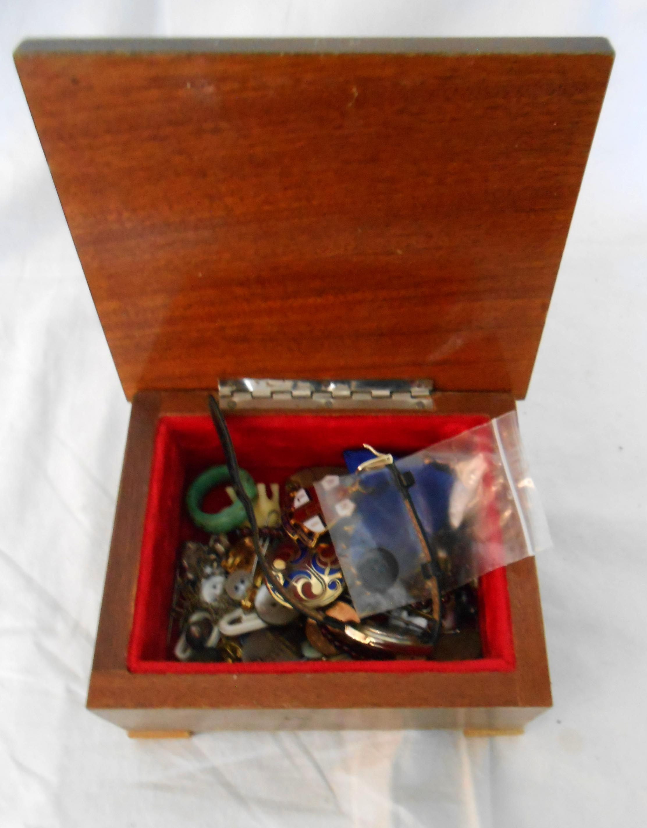 A decorative wooden box containing a modern Limit lady's wristwatch and modern RNLI jewels, etc.