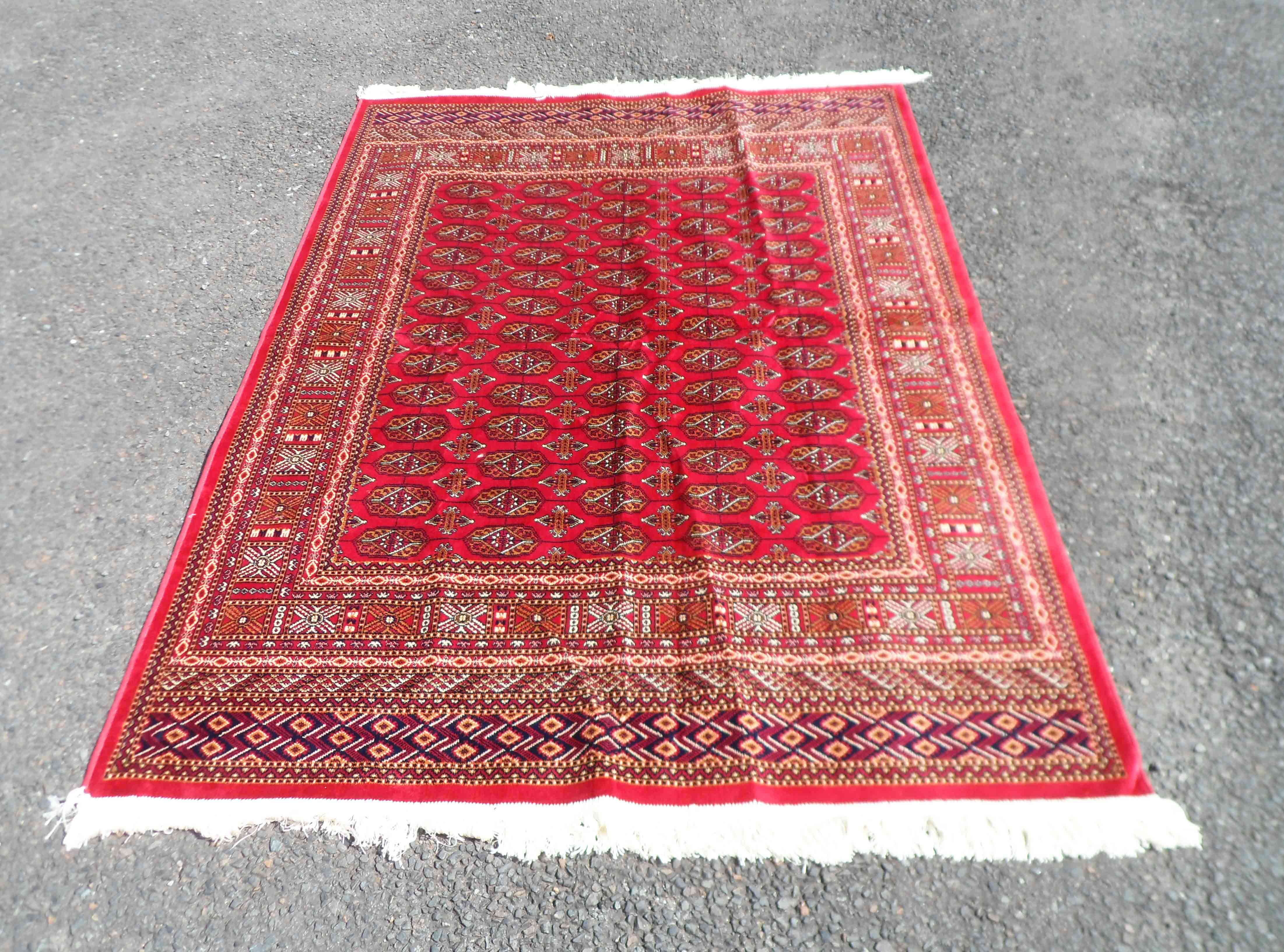 A late 20th Century red machine made Kashan rug, with central repeat gul decoration and geometric