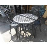 A black painted cast metal table with two chairs - paint flaking