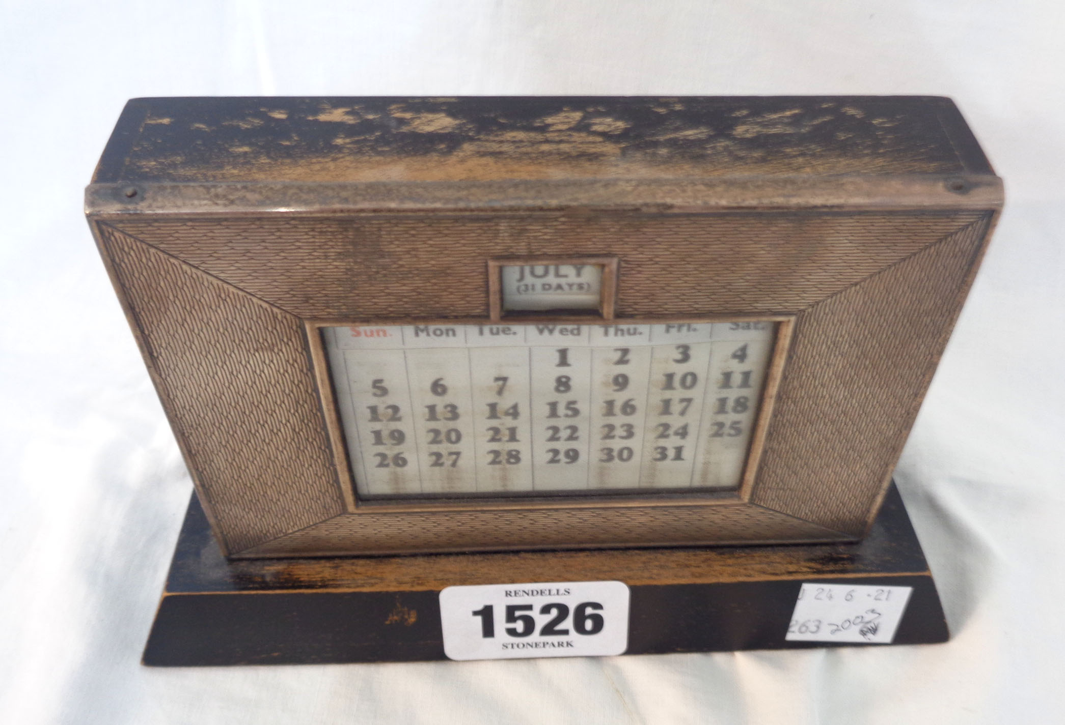 A vintage silver fronted desk calendar with engine turned decoration and painted wood base