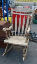 A wooden lathe back elbow rocking chair with carved decoration set on turned supports