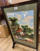A vintage stained wood framed fire screen with decorative woold work panel under glass