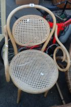 A bentwood elbow chair with rattan back and seat set on tapered legs