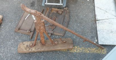 An antique iron and wood cart jack