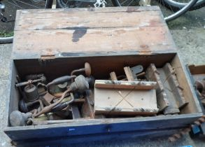 A wooden box containing assorted tools including planes, moulding planes, braces, etc.