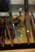 A wooden drawer containing assorted tools including hand drills, knife sharpener, cobbler's last,