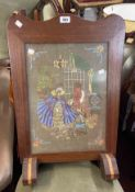A 1930's mixed wood fire screen with embroidered panel under glass, set on Art Deco feet