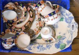 A small crate containing an Imari pattern part tea set and transfer printed meat plate