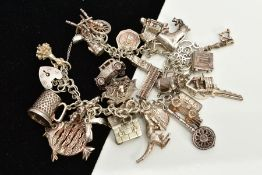 A WHITE METAL CHARM BRACELET, suspending twenty-seven charms in forms such as a house, web,boots,