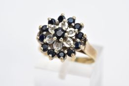 A 9CT GOLD SAPPHIRE AND DIAMOND CLUSTER RING, the large slightly raised cluster set with a central