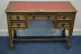 AN OLD CHARM OAK DESK with a bright red and gilt tooled leather inlay top five drawers on turned