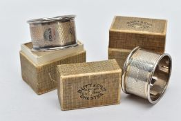TWO CASED SILVER NAPKIN RINGS each of an engine turn design engraved initial 'E' on one and 'R' on