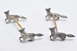 A PAIR OF WHITE METAL KNIFE RESTS, each rest modelled with two foxes to each end with a worn gilt