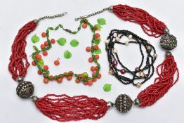 THREE GLASS BEAD NECKLACES, to include a green glass leaf and orange ball bead necklace on a white