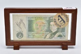 A FRAMED BANK OF ENGLAND 'ONE POUND NOTE', within a wooden frame, raised on two block feet, the note