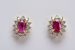 A PAIR OF 18CT GOLD RUBY AND DIAMOND CLUSTER EARRINGS, each designed with a central claw set, oval