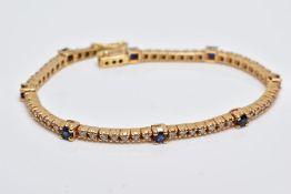 A YELLOW METAL DIAMOND AND SAPPHIRE LINE BRACELET, set with round brilliant cut diamonds, total