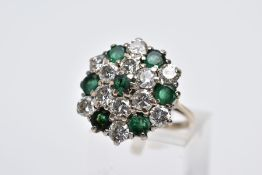 AN EMERALD AND DIAMOND CLUSTER RING, the yellow metal ring designed with a large slightly raised