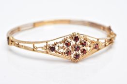 A 9CT GOLD GARNET HINGED BANGLE, of a floral and beaded openwork design, the central flower set with