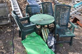 A GREEN PAINTED METAL CIRCULAR GARDEN TABLE on shaped legs together with four green plastic stacking