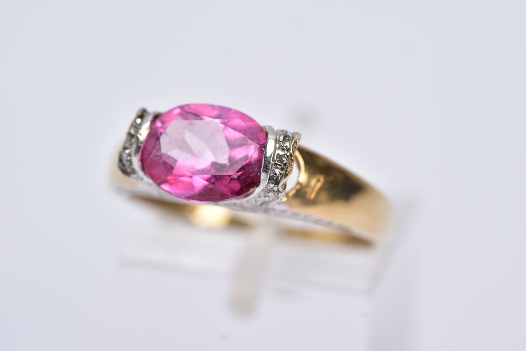 A 9CT GOLD PINK TOPAZ RING, designed with a tension set, oval cut pink topaz, single cut diamond