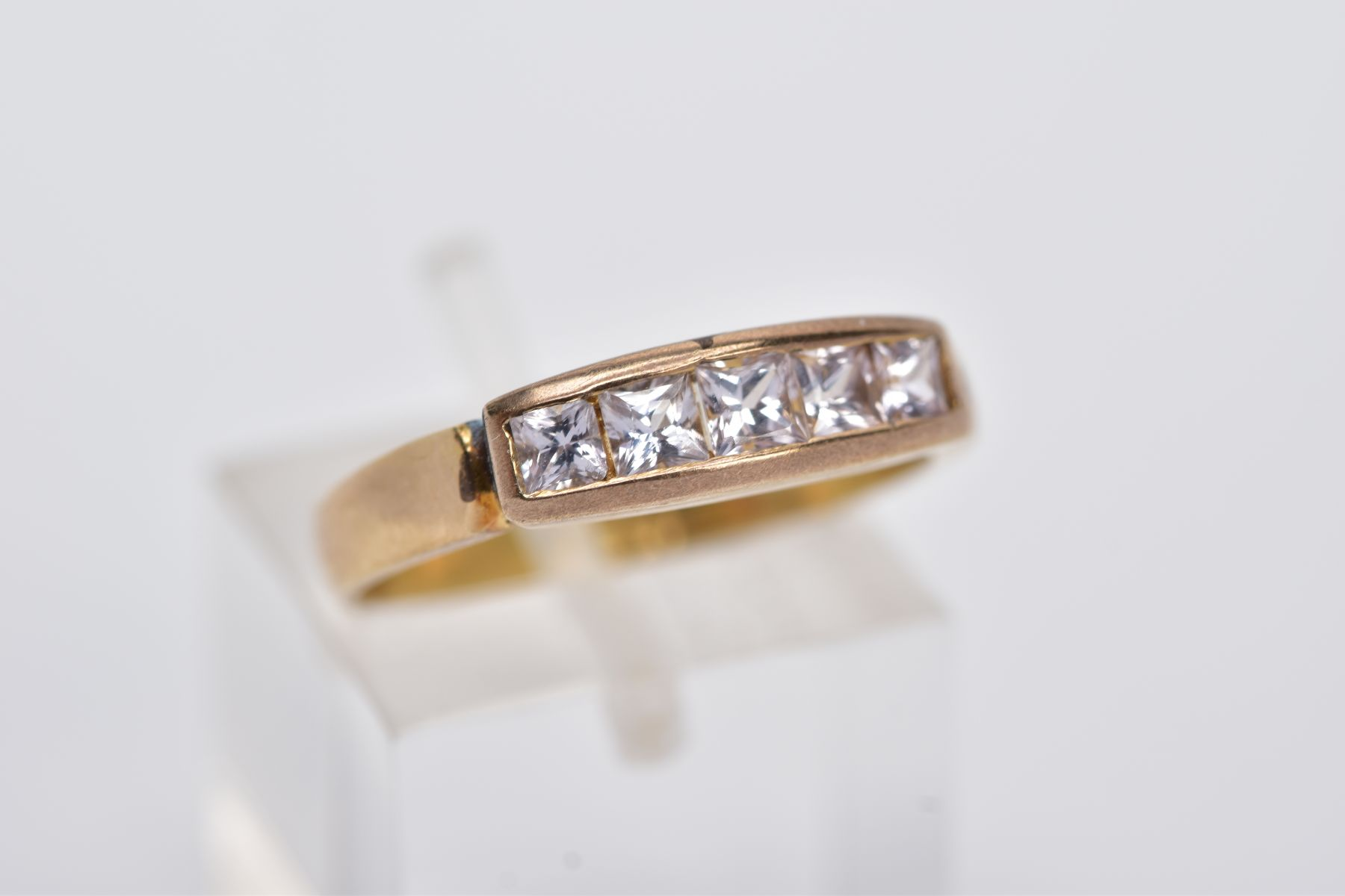 A YELLOW METAL HALF HOOP RING, designed with a row of graduated square cut colourless stones, - Image 4 of 4